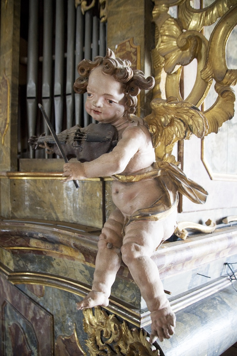 The sculpture of a putto on the organ case in Sladka gora (Institute for the Protection of Cultural Heritage of Slovenia, photo by Valentin Benedik, 2018)